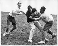 Three men engage in a pick-up game of tackle football.