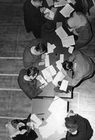 An overhead shot of student registration in Room 256 shows men and women using inkwells and pens to register for classes.