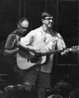 A man plays an acoustic guitar at the 1965 Frosh Camp.