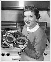 Mrs. Ralph (Victoria) Amaden, runner-up in Mrs. Wayne State University, 1957, holds a platter of food and garnishes.