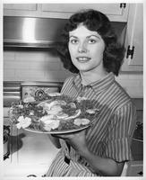 Portrait of Mrs. Richard R. (Norma J.) Baker from the Mrs. Wayne State University file. She is holding a platter of food.