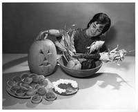 A woman poses with Halloween tabletop food display.