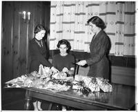 Three woman are wrapping fruit cakes for an annual bake sale for Phi Epsilon Omicron.