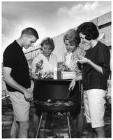 One man and three women are grilling hamburgers at Joy Dormitory.