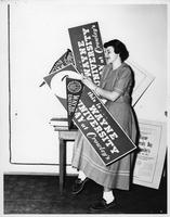 A woman gathered Wayne University pennants and signs from the Wayne University day at Crowley's.