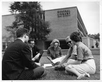 Students sitting and studying on the grass outside of the General Library
