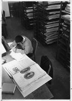 A man istudies in the periodicals section of the library.