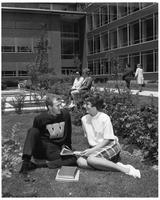 A couple reads a book on the grass in front of State Hall.