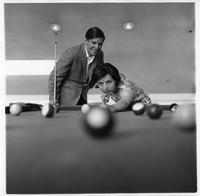 A man and woman play pool.