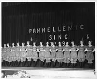 A Panhellenic group of singers and dancers perform on stage.