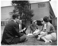 A group of students sit on the grass studying in front of the General Library.
