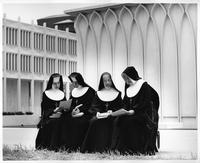 Four nuns look over books and notebooks in front of the DeRoy Auditorium.