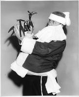 A man in a Santa outfit holds two cardboard reindeer