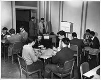 A group of students play a card game, perhaps spades, hearts, or bridge.