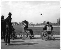 A group of athletes in wheelchairs practice the discus toss.