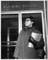 An African-American woman holds her books in front of the Alumni House.