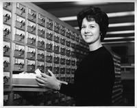 A woman uses the card catalog system in a library.