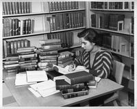 A woman student studies at a desk in the library.