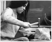 A woman student in corduroy pants uses a rock hammer to study the geology of a rock.