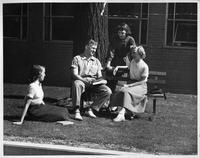 Four students lounge outdoors, possibly in front of Community Arts.