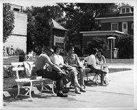 Students lounge on benches in a courtyard adjacent to the Rands House.