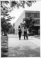 Two women in bellbottoms walk in front of the College of Education Building.