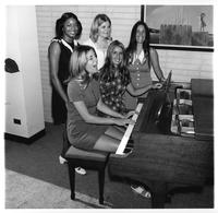 Five women sing at a piano.