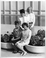 Four women students pose in front of the DeRoy Auditorium.
