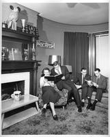 Four people lounge reading a guestbook in front of a fireplace-strewed with trophies and a stuffed owl with ping-pong paddles for ears.