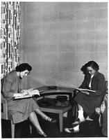 Two women study at a table.