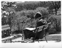 A woman studies in solitude on a park bench.