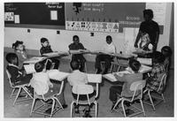 A group of young children sit in a classroom.