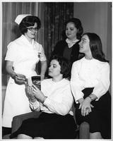 A nurse reviews a book with three women students.