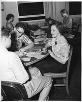 Coeds study at a table while others use typewriters in the background.