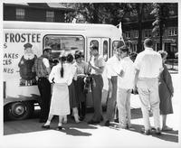 A group gathers around a food truck (Ice Cream Truck) while one man plays an acoustic guitar.