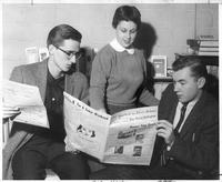 Three students review a copy of The Daily Collegian.