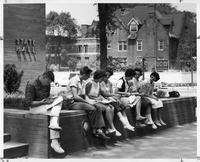 A group of students sit outside of State Hall.