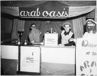 "A festival booth named ""Arab Oasis"" advertises Vernors Ginger Ale."