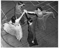 Two men and two women are engaged in a group dance on a basketball court.