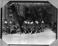 A photo of visiting nurses, the Alger Club, leaving a building.