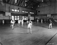 A group of students playing volleyball in the gym.