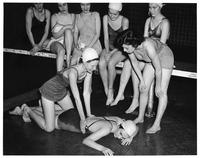 A group of students in swimming attire observe as CPR is taught. Probably 1935.