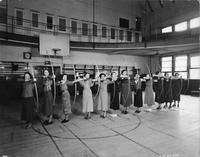 A group of women practice archery in the gym at Old Main.