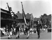 The R.O.T.C. color guard parades down the street while a marching band brings up the rear.
