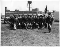 R.O.T.C. in formation in a field in front of the Pittsburgh Plate Glass Company Building with water tower. Likely Kelsey Field.