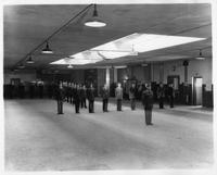 R.O.T.C. members in formation inside a building.