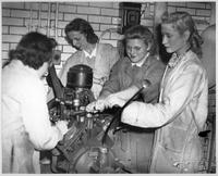 Four women work on an engine in the Engineering Lab in 1946.