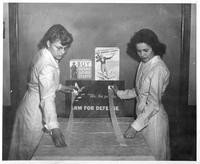 Two women at a wartime fund raising station.