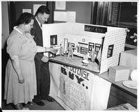 Asst. Prof. Mabel Lange Smith and Frank N. Isbey, chairman of the Michigan State savings Committee [sic], inspect part of an exhibit depicting the historical background for national defense and the various activities now going on in Detroit if furtherance of the program.