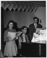 Three people at a piano as part of a wartime fund raising exhibit.